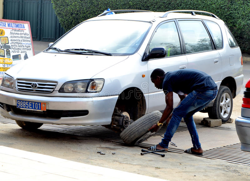 WORLDWIDE DAY TO COMBAT COUNTERFEITING. Young African during the world day of counterfeiting getting rid of counterfeit tires from his car launching a strong royalty free stock image