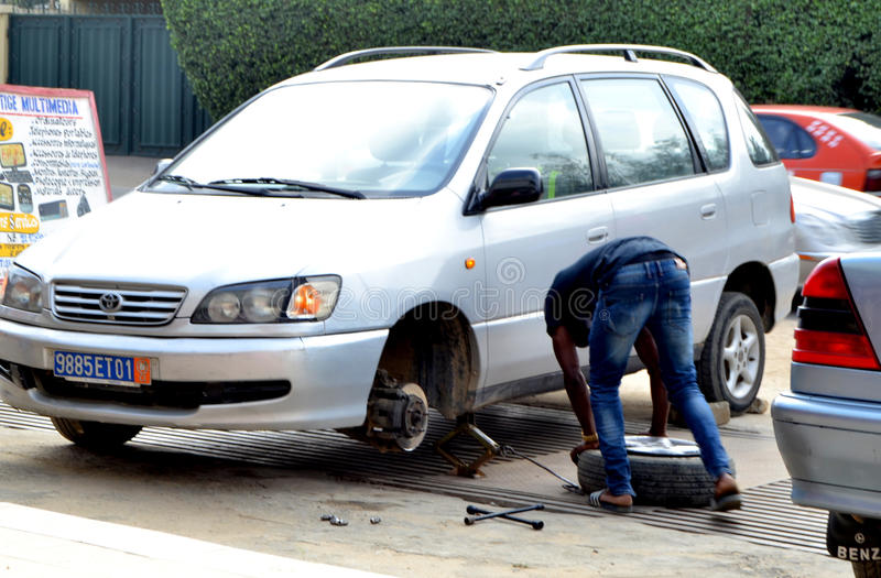 WORLDWIDE DAY TO COMBAT COUNTERFEITING. Young African during the world day of counterfeiting getting rid of counterfeit tires from his car launching a strong royalty free stock images