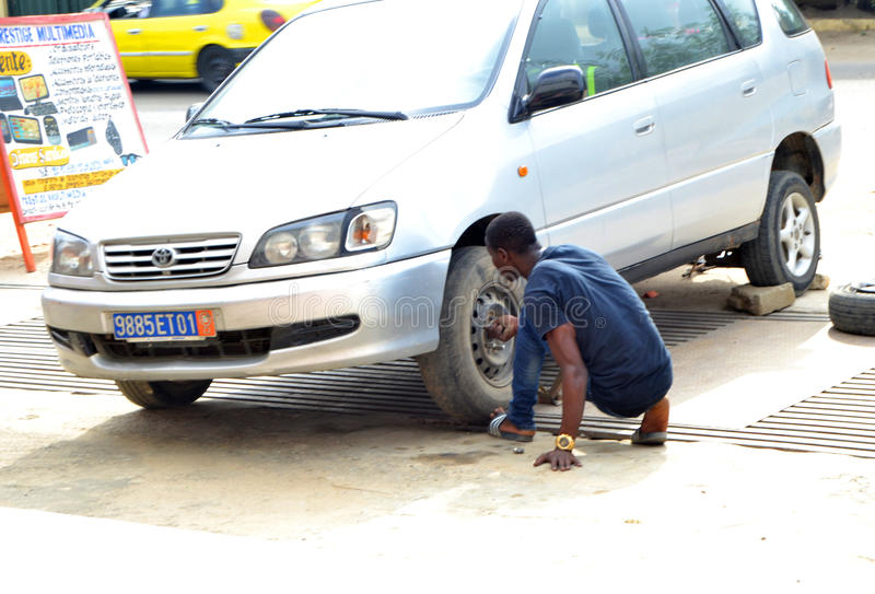 WORLDWIDE DAY TO COMBAT COUNTERFEITING. Young African during the World Day of Counterfeiting getting rid of the counterfeit tires of his car to raise public royalty free stock photography