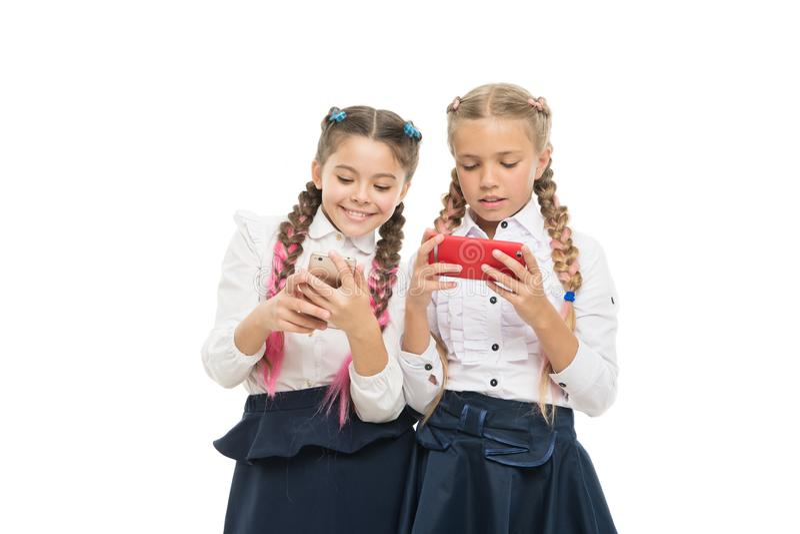 Worldwide net. Internet resource has hazards for kids. Girls school uniform surfing internet. Schoolgirls use mobile. Internet smartphone. School application stock photo