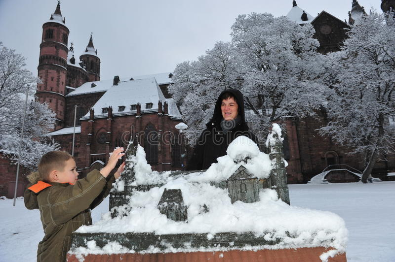 Worms cathedral. Frankfurt, Germany - December 20, 2010: Mother and son playing with a model of Worms cathedral in snow stock photography