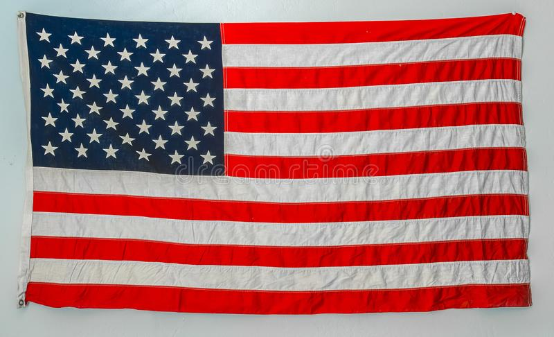 Worn american flag hanging from wall. On a blank white wall stock photography