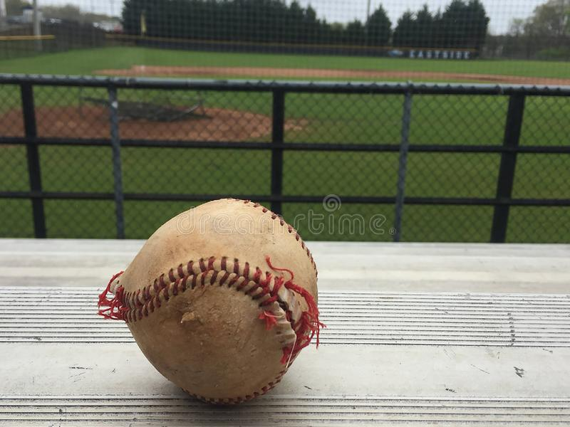 Worn baseball on bleachers. Worn and busted baseball with unraveling red stitches on bleachers overlooking baseball field stock photography