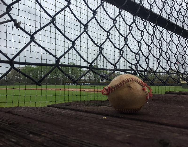 Worn baseball on wooden deck above baseball field royalty free stock images