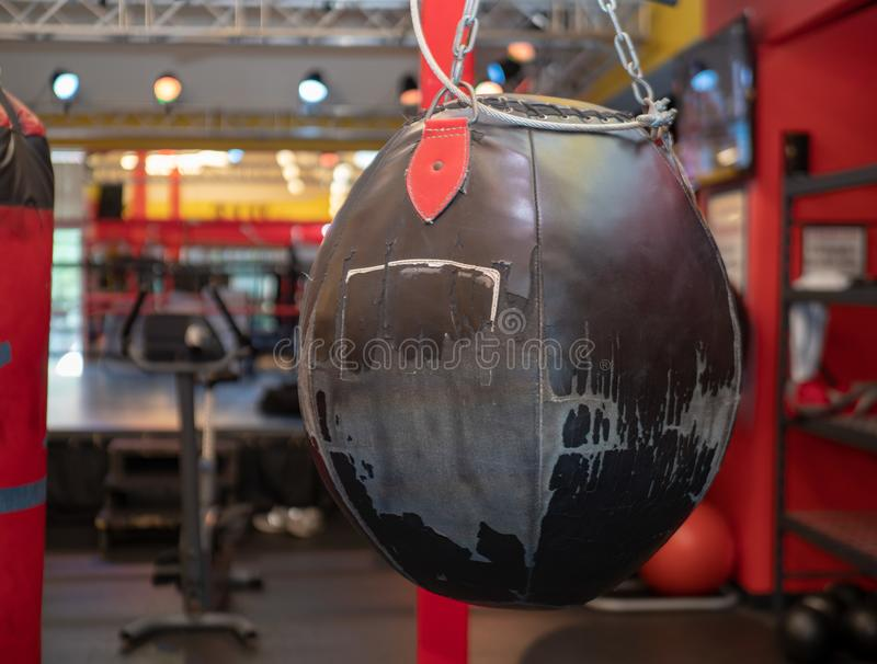 Worn, black leather wrecking ball style heavy bag hanging at a boxing gym. A worn, black leather wrecking ball style heavy bag hanging at a boxing gym royalty free stock image