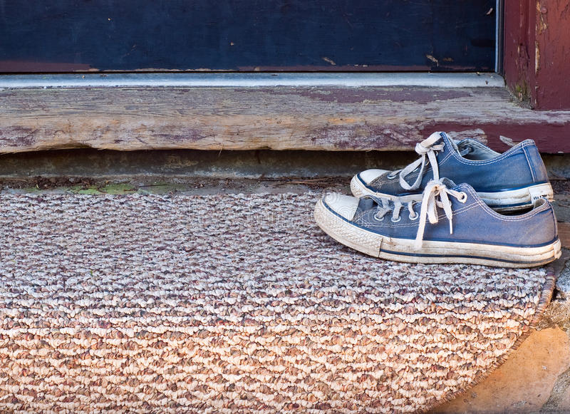 Worn Blue Shoes on doormat stock photography