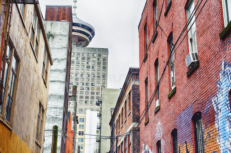 Worn buildings in the downtown core of Vancouver, B.C., Canada. Alley lined with old brick buildings located in the downtown core stock image