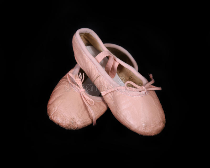 Worn Children's Ballet Shoes. A pair of very worn children's ballet shoes on black royalty free stock photo