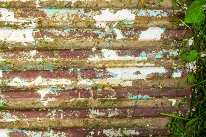 Worn corrugated metal steel sheeting with peeling paint with green grass and leaves side. Background of the old rust sheet. Grunge stock images