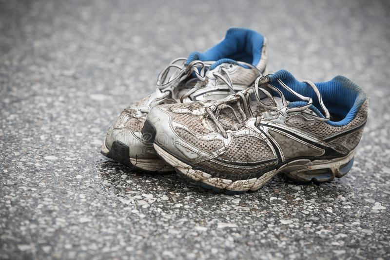 Worn, dirty, smelly and old running shoes on a tarmac road stock image