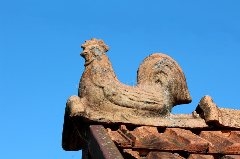 Worn down dilapidated edge roof tile shaped like sitting rooster overlooking surroundings stock photography