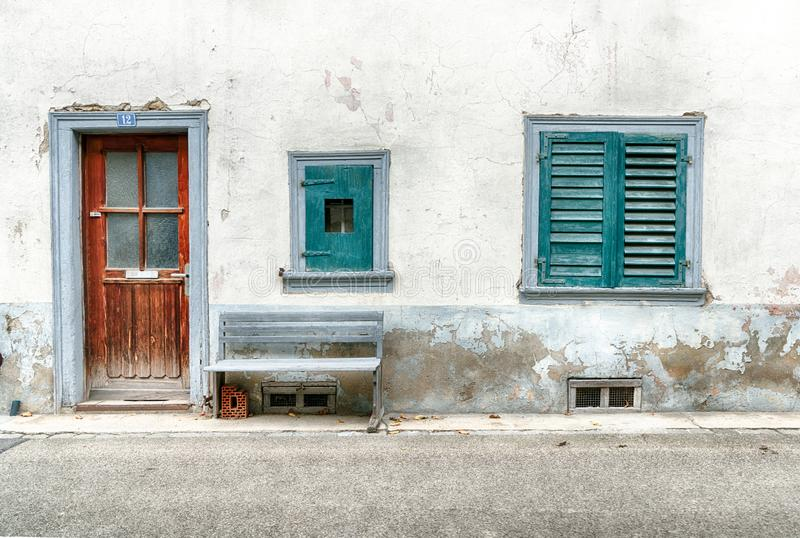 Worn and faded house front detail with two windows and old wooden door and rickety bench on the roadside royalty free stock photography