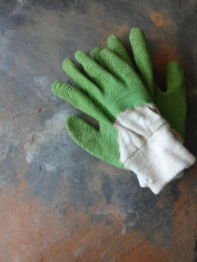 Worn Garden Gloves. Used Garden Gloves - Against a Slate Background royalty free stock photo