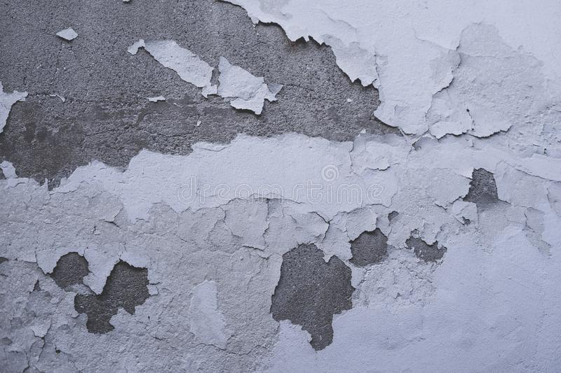 Worn house wall peeling off wall paint. Worn house wall peeling off white wall paint royalty free stock images