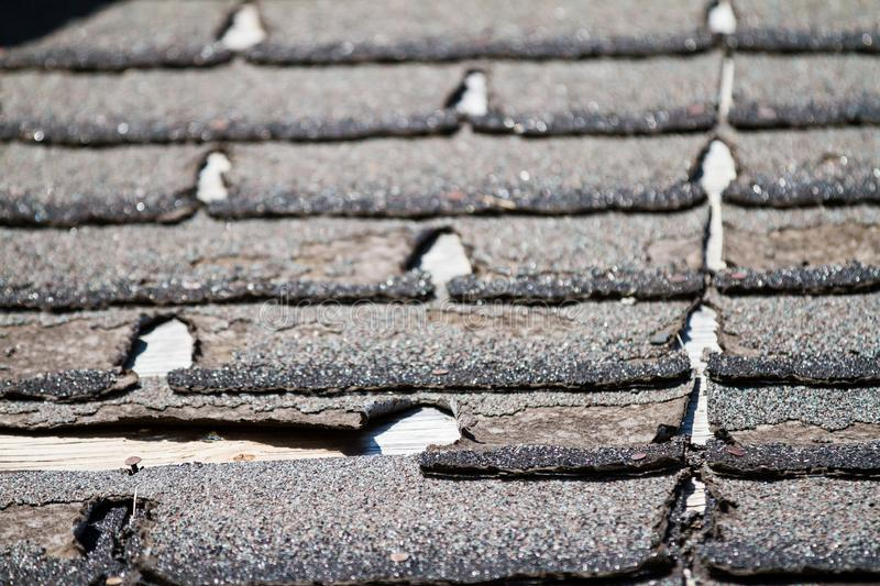 Worn-out asphalt shingles on a roof. Shingles needing replacement or repair stock photo