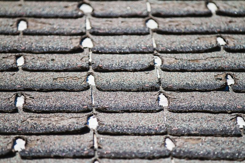 Worn-out asphalt shingles on a roof. Shingles needing replacement or repair royalty free stock image