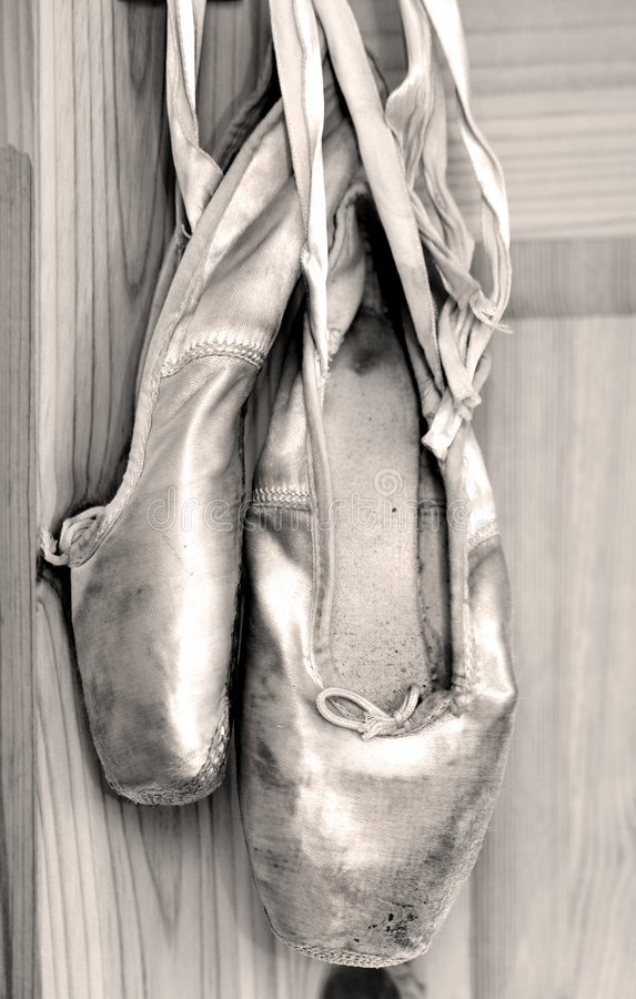 Worn out ballet shoes. A pair of worn out ballet shoes in sepia royalty free stock photography