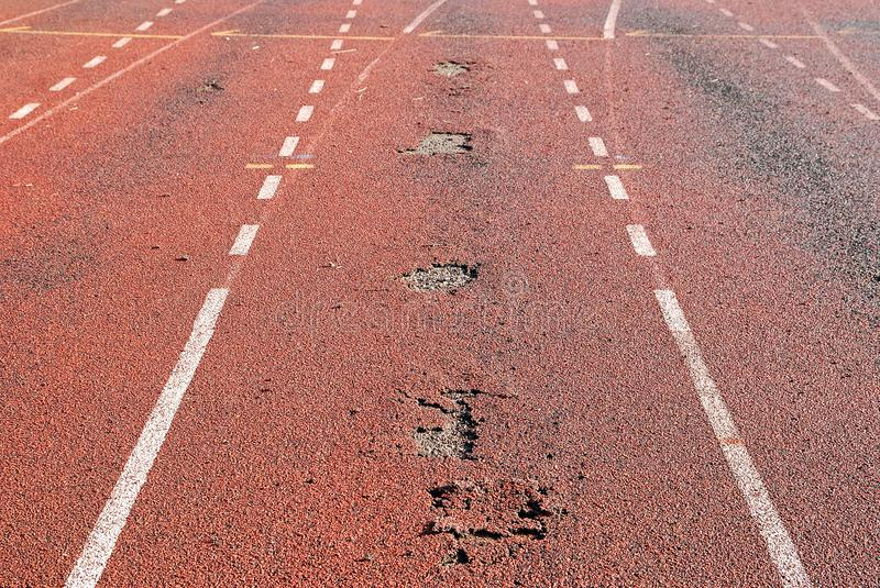 Worn out running track of a stadium. Stripping surface of stadium synthetic running track. Maintaining the running track of a stadium is essential to ensure top royalty free stock photography