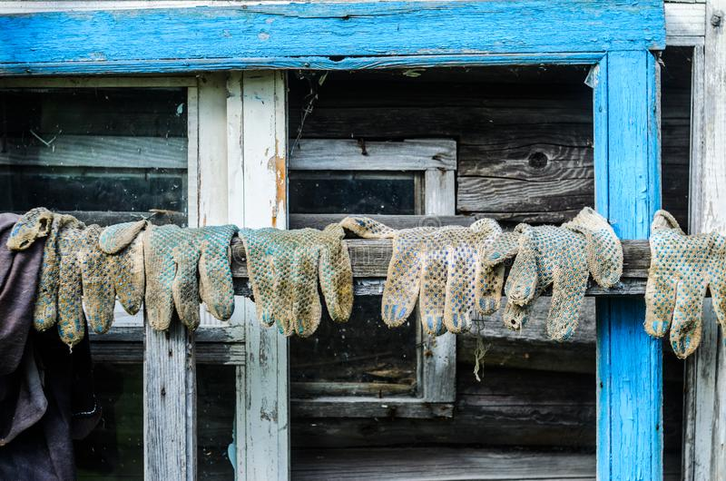 Worn out Working Gloves Background. Worn Out Dirty Working Gloves Hanging on the Background of the Wooden Facade of the Barn. Farm Work Concept royalty free stock photography