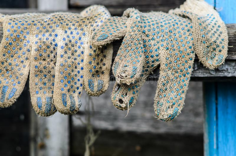 Worn out Working Gloves Background. Worn Out Dirty Working Gloves Hanging on the Background of the Wooden Facade of the Barn. Farm Work Concept royalty free stock photo