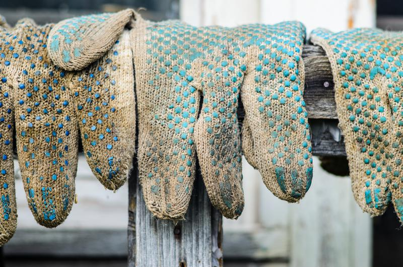 Worn out Working Gloves Background. Worn Out Dirty Working Gloves Hanging on the Background of the Wooden Facade of the Barn. Farm Work Concept stock images