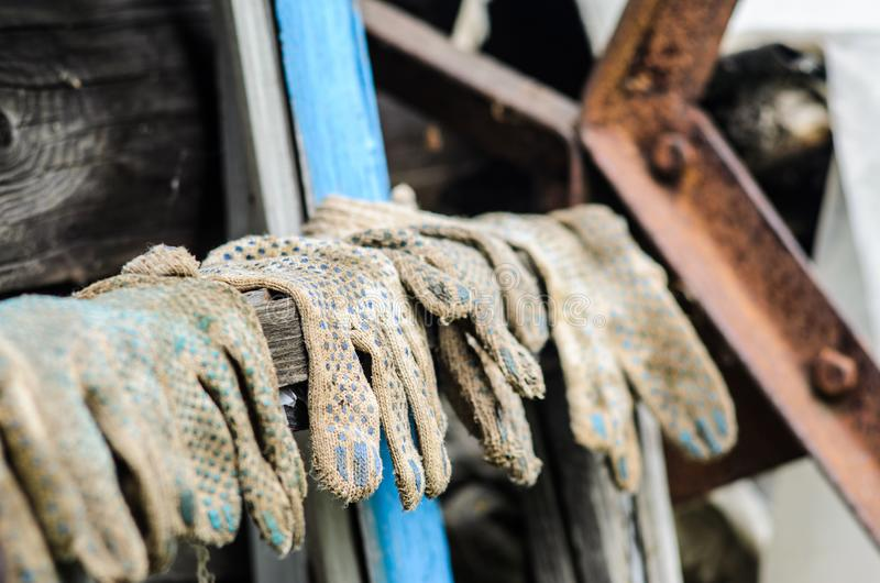 Worn out Working Gloves Background. Worn Out Dirty Working Gloves Hanging on the Background of the Wooden Facade of the Barn. Farm Work Concept stock photography