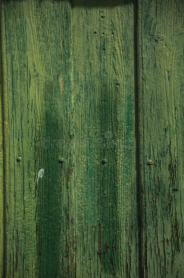 Worn planks with peeling paint in an old door. Close-up of worn planks with peeling paint in an old green door, forming a singular background near Monsanto stock images