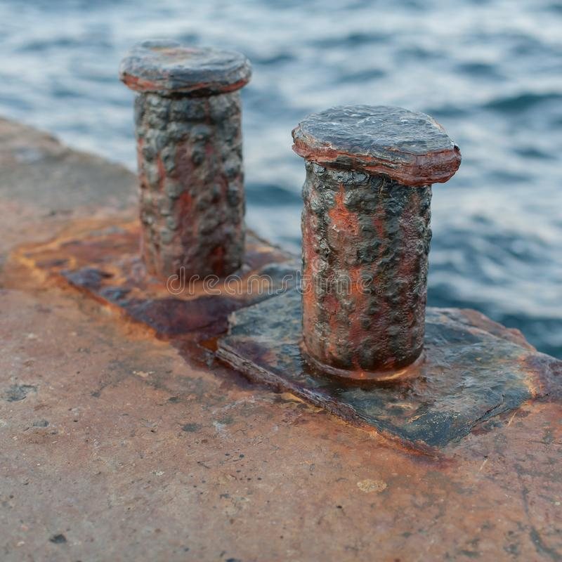 Worn rusty bollards on old concrete pier. Fragment of old jetty. Worn rusty bollards on old concrete pier stock photo