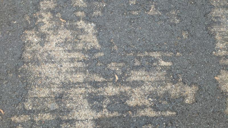 Worn tarmac over concrete. Tarmac on the surface of concrete with away over time stock photos