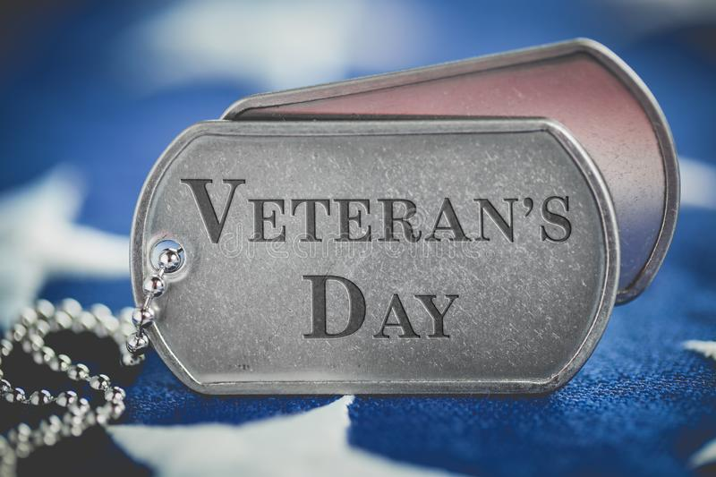 Worn US American dog tags on USA flag with Veteran`s Day text royalty free stock photography