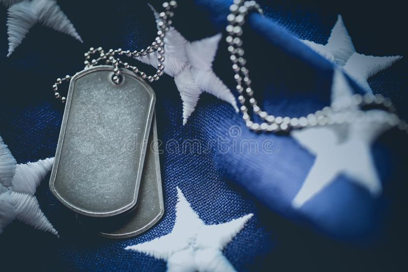 Worn USA military dog tags close up on US American flag with space for text stock photos