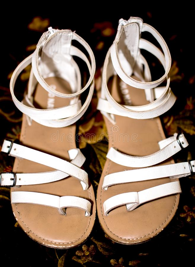 Worn White Summer sandals with lots of straps. Vintage girl shoes top view on dark background royalty free stock image