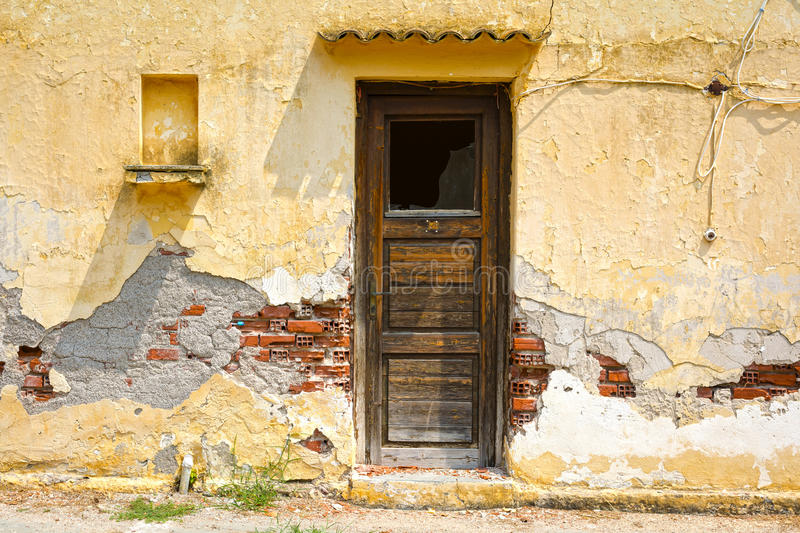 Worn wooden door in a weathered wall stock photo