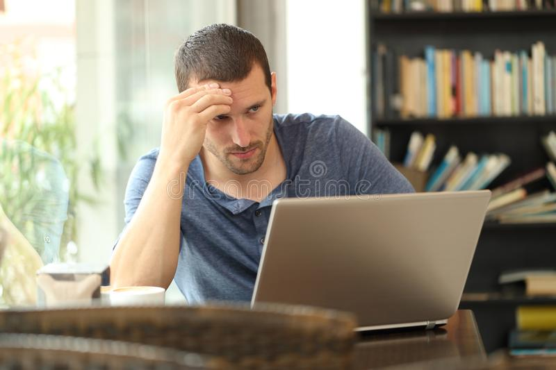 Worried adult man checking laptop content in a coffee shop. Worried adult man checking laptop online content sitting in a coffee shop royalty free stock images