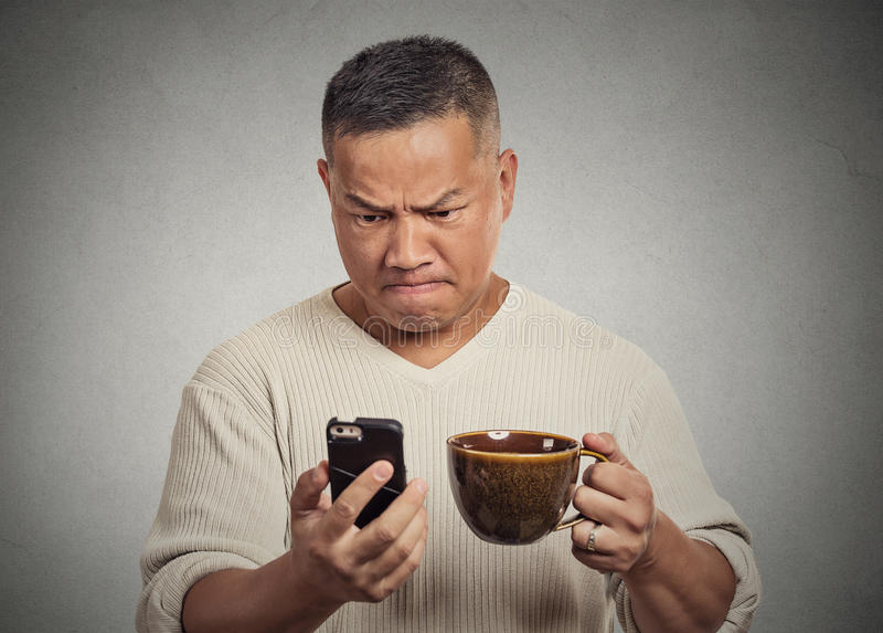 Worried angry frustrated man reading bad news sms on smartphone royalty free stock photos