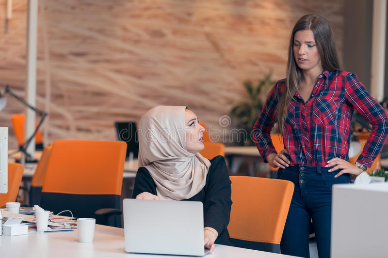 Worried arabic businesswoman wearing hijab receiving a notification. Worried businesswoman receiving a notification from a colleague in her workplace at office stock photography