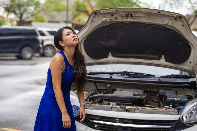 Worried Asian Japanese woman in stress stranded on street roadside with car engine failure having mechanic problem needing repair. Young desperate and worried stock images