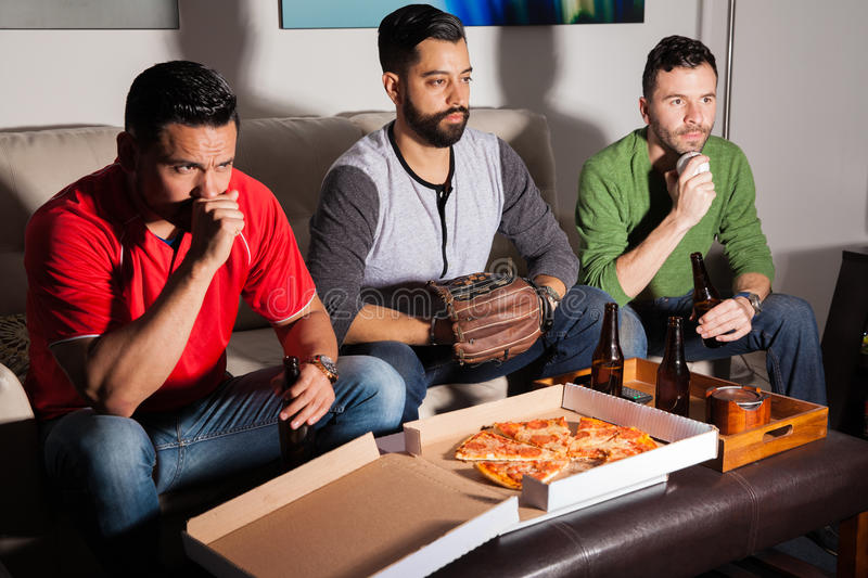Worried baseball fans watching a game. Three worried friends watching a baseball game on TV at night while drinking some beer and eating pizza stock photography