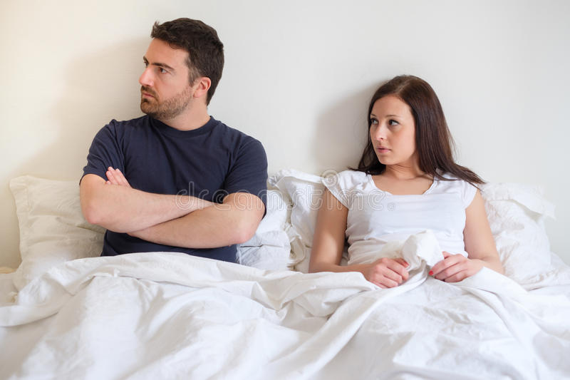 Worried and bored lovers couple after arguing. Lying in the bed stock images