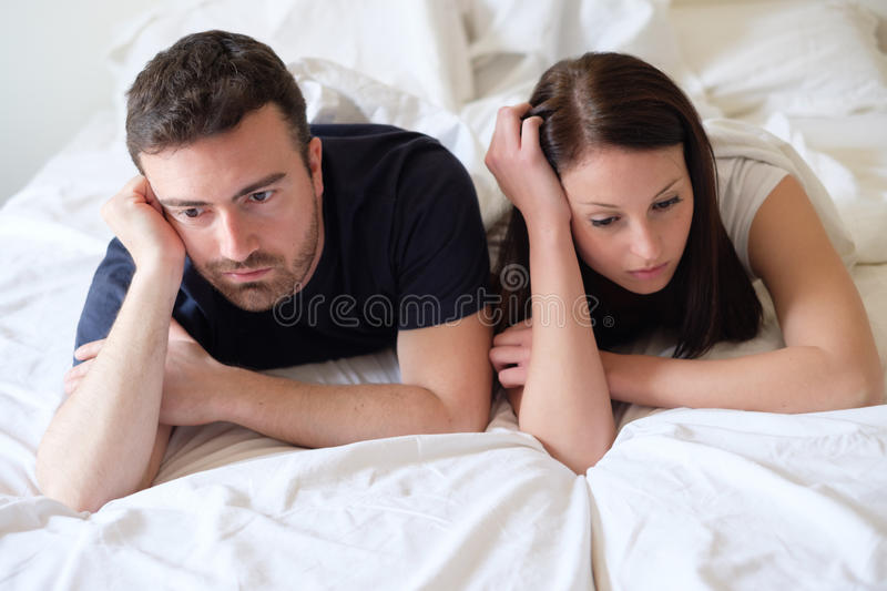 Worried and bored lovers couple after a fight lying in bed. Worried and bored lovers couple after a fight lying in the bed stock image