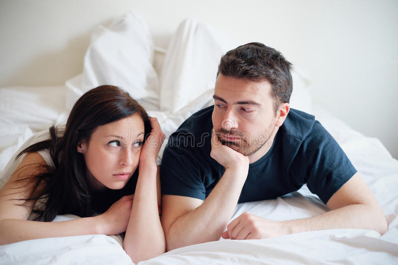 Worried and bored lovers couple after a fight lying in bed. Worried and bored lovers couple after a fight lying in the bed stock photography