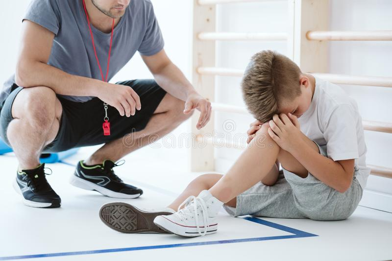 Worried boy during classes. Worried boy and a coach during physical education classes stock images