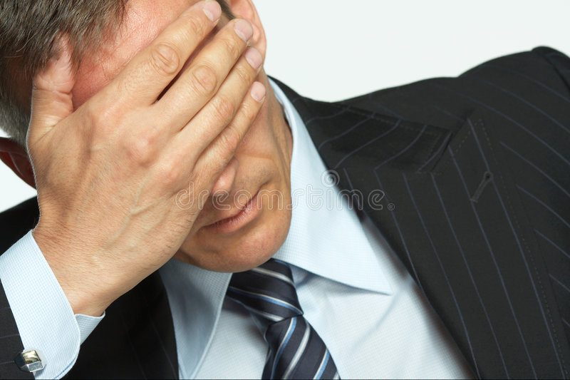 Worried businessman. A man holds his head in his hand with worry royalty free stock photography