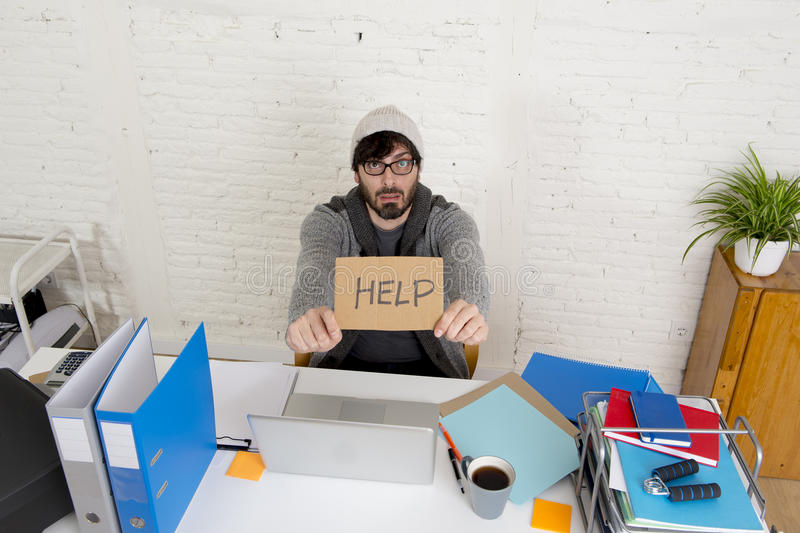 Worried businessman in cool hipster beanie look holding help sign working in stress at home office. Young worried businessman in cool hipster beanie look holding stock images