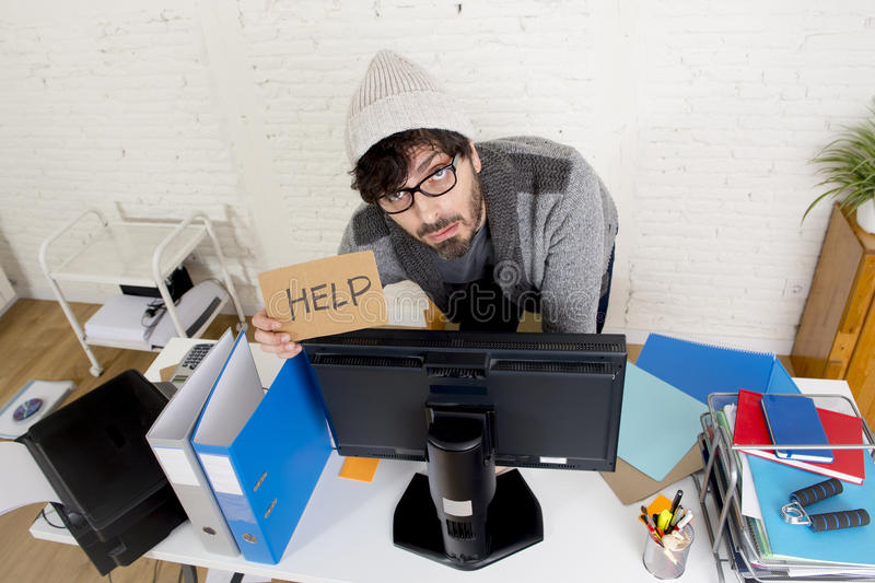Worried businessman in cool hipster beanie look holding help sign working in stress at home office. Young worried businessman in cool hipster beanie look holding royalty free stock photos