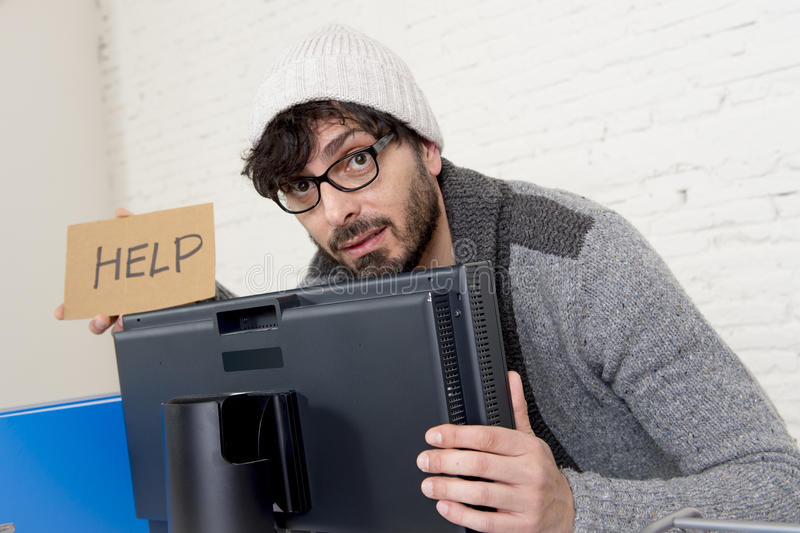 Worried businessman in cool hipster beanie look holding help sign working in stress at home office. Young worried businessman in cool hipster beanie look holding stock photo