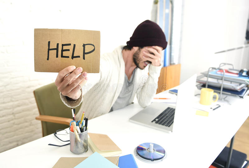 Worried businessman in cool hipster beanie look holding help sign working in stress at home office. Young worried businessman in cool hipster beanie look holding stock image