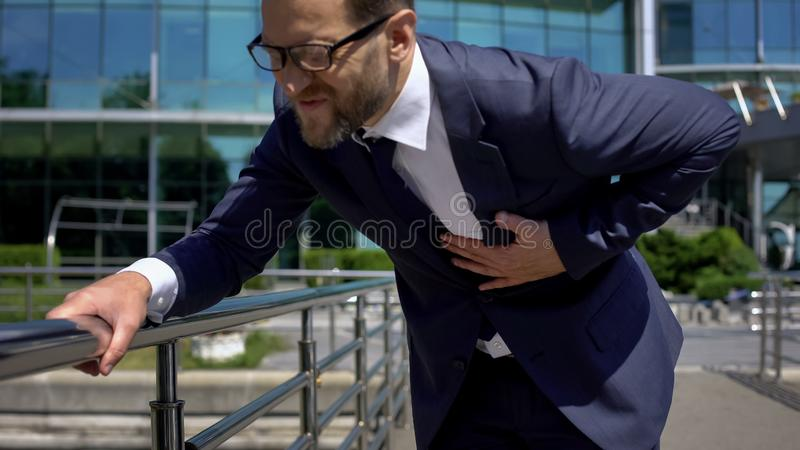 Worried businessman having heart attack outdoors, strong chest pain, first aid stock image