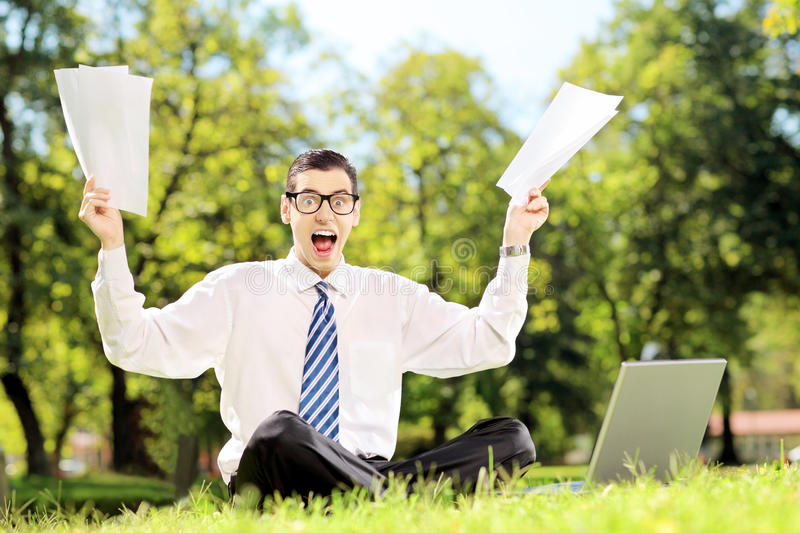 Worried businessman holding documents and shouting seated on a g royalty free stock photos