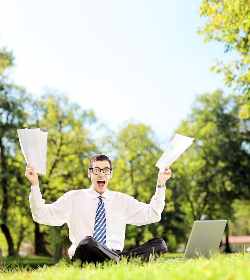 Worried businessman holding documents and shouting seated in a p stock photography